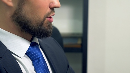 Closeup of lips. portrait of a bearded man in a suit and tie talking. face profile