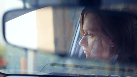 Reflection of a womans face in the rearview mirror, a woman prepares a rear-view mirror before driving Zdjęcie Seryjne