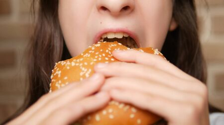close. childs mouth. girl eating a hamburger