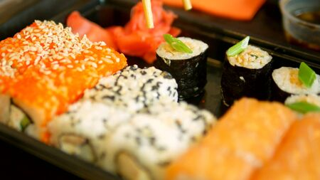 close-up. someone takes sushi with chopsticks, rolls and dips in soy sauce