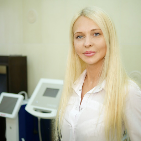 Young attractive female doctor in the office on the background of medical equipment.
