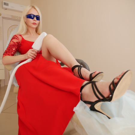 Beautiful young woman in a luxurious red dress makes herself laser hair removal in the spa salon. beautiful cosmetologist