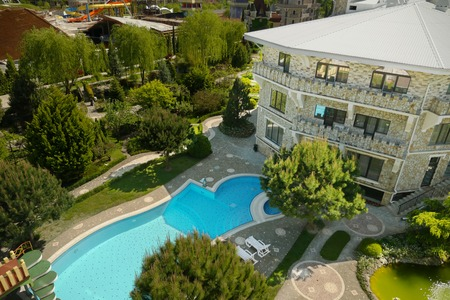 modern luxury hotel in the Tudor style with a blue pool at the foot, with beautiful well-kept trees, view from above