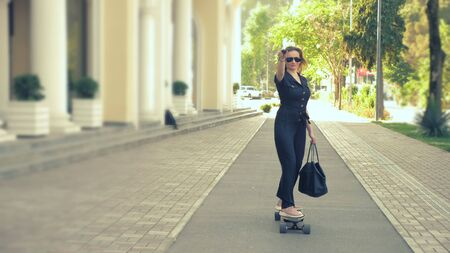 Modern business woman in a black jumpsuit in pink sneakers, sunglasses and a black bag riding on an electric board along a city street, depicting a super man, stretching one arm forward. The concept of the strange adventures of people Stockfoto