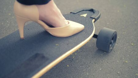 close-up. womens beige shoe on a black skate board. Modern business woman in beige pumps shoes, rides on an electric board along a city street. The concept of achieving the goal and leadership Фото со стока