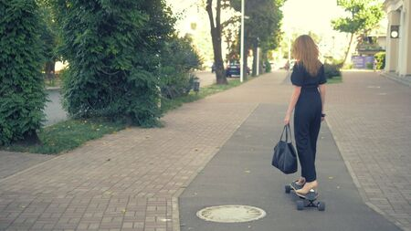 A modern business woman in a black jumpsuit in beige pumps shoes, and with a black bag riding on an electric board along a city street. Concept of strange people adventures