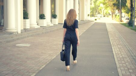 A young woman with long dark blond hair, dressed in a black jumpsuit, beige leather shoes, with a black bag walking down the street, the camera follows her, view from the back Фото со стока