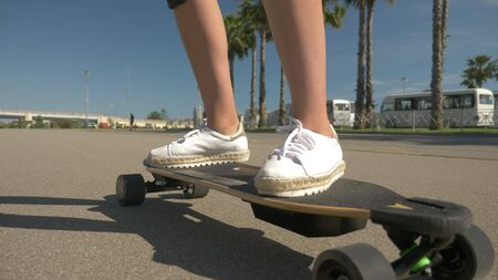 girl riding an electric skateboard in a beautiful park with tall palm trees
