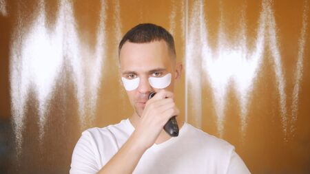 Portrait of a handsome man with an eye mask that shaves with an electric razor in the bathroom. Metrosexual concept Stockfoto