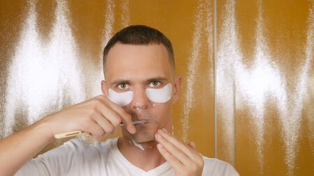 Portrait of a handsome man with a mask under the lower eyelid, which is shaved with a straight razor in the bathroom. Metrosexual concept