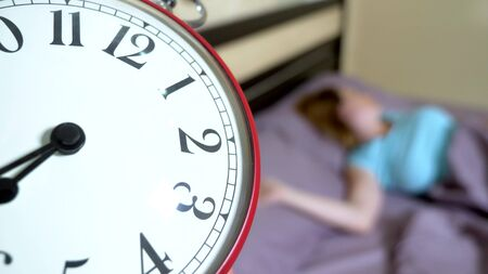 Red alarm clock close-up, on a blurred background, the girl is angry that the alarm clock has rung Banco de Imagens