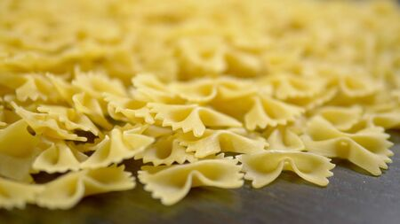 raw pasta, Farfalle closeup on wooden table.