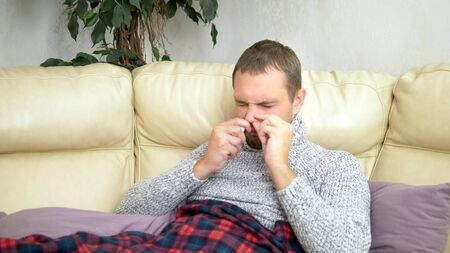 Handsome man with a runny nose uses a nose spray at home, sitting on a sofa in the living room in a sweater and under a blanket Banco de Imagens