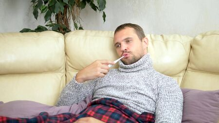 Young sick man in a sweater under a plaid with a fever checks his temperature with a thermometer at home