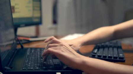 The concept of multitasking or cheating in social networks. One woman types simultaneously on three keyboards. hand closeup.