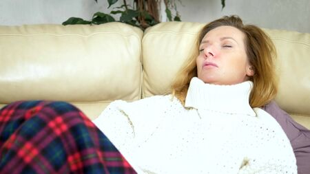 Caucasian woman, with paper napkin sneezing, in a sweater under a blanket on the couch, experiencing allergy symptoms, caught a cold.