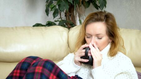 sick woman in a sweater under a blanket drinking a hot drink on the sofa in the living room