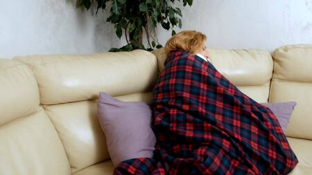 woman in a house on the sofa lying under a plaid at home suffering from cold and fever. The concept of cold and flu virus 写真素材