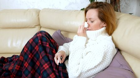 Beautiful woman with a runny nose uses a nasal spray at home, sitting on the sofa in the living room, in a sweater and under a blanket Banco de Imagens