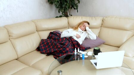 Young sick woman in a sweater under a plaid with a fever checks her temperature with a thermometer at home