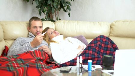 concept of cold and flu virus, epidemic. husband and wife with fever lie on the living room sofa in sweaters and under blankets