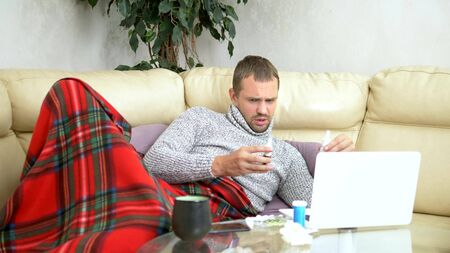 man with a cold sitting on the sofa in a sweater and a plaid calling his doctor on a laptop via video link. 免版税图像