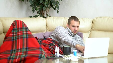 man with a cold sitting on the sofa in a sweater and a plaid calling his doctor on a laptop via video link. 写真素材