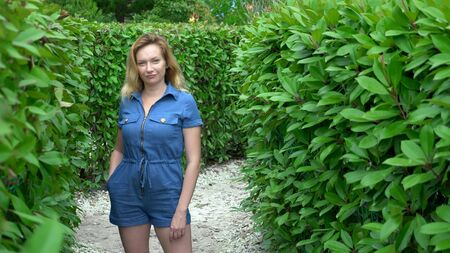A woman in a short denim jumpsuit standing in the middle of a hedge maze on a sunny summer day. Looks at the camera. Stockfoto - 128601471