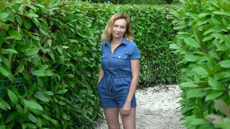 A woman in a short denim jumpsuit standing in the middle of a hedge maze on a sunny summer day. Looks at the camera. Stockfoto - 128601492