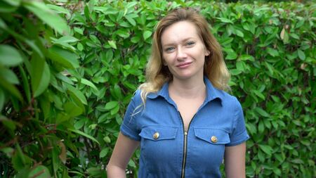 A woman in a short denim jumpsuit standing in the middle of a hedge maze on a sunny summer day. Looks at the camera. Stock fotó