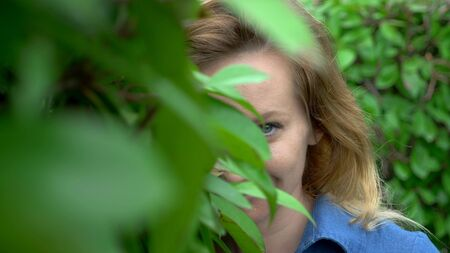 A woman in a short denim jumpsuit standing in the middle of a hedge maze on a sunny summer day. Looks at the camera.