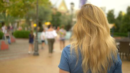 A beautiful young blond woman walks around the city and looks around with interest, the camera follows her against the background of a moving crowd of people, blurry