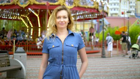 summer time concept. A woman happily looks into the camera with a kind smile on the background of the carousel in an amusement park
