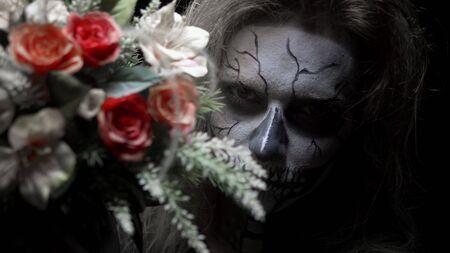 concept, beautiful makeup for halloween. Portrait of a young sexy girl with make-up of a skull and a bouquet of flowers.