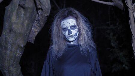 Konzept des Horrors, Geisterfrau im Wald. Schöne Frau mit Make-up-Skelett in einem beängstigenden Wald.