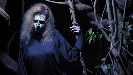 concept of horror, ghost woman in the forest. Beautiful woman with make-up skeleton in a scary forest.
