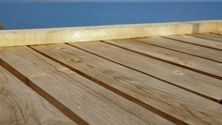 striped wooden terrace sloping with a background of sky and sea.