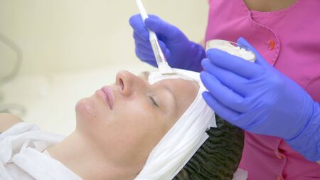 The concept of cosmetology. Close-up of a beautician applying a white mask with a brush on a womans face. Standard-Bild