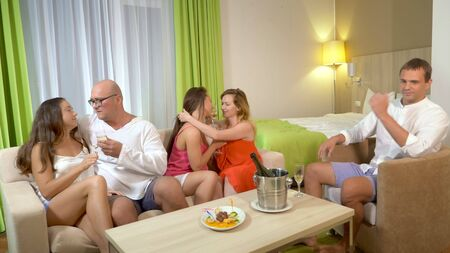Konzept Sexclubs, Swingclubs, Lifestyleclubs, formelle, informelle Gruppen. eine Gruppe von Menschen trinkt Champagner und kuschelt sich in einem gemütlichen Wohnzimmer.