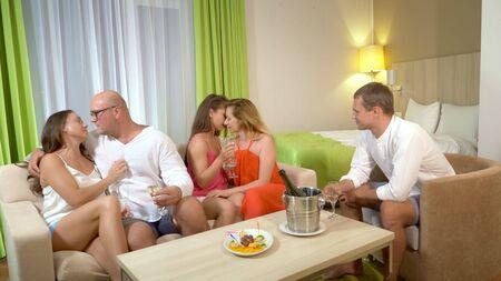 Concepto Clubes de sexo, clubes de swing, clubes de estilo de vida, grupos formales e informales. un grupo de personas beben champán y se abrazan mientras se relajan en una acogedora sala de estar.