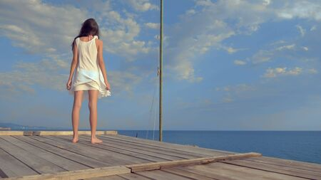 teenage girl in a white dress with long hair looks thoughtfully into the sea, being on a wooden terrace above the sea. wind develops hair