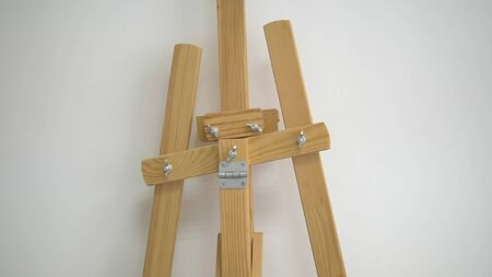 Empty wooden easel , close-up against a white wall. Фото со стока