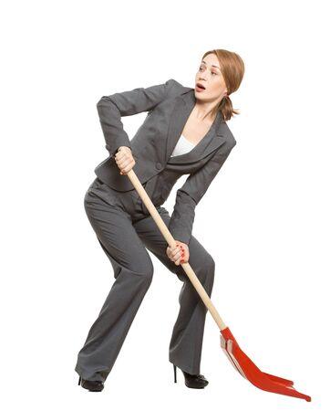 donna dai capelli rossi in giacca e cravatta, impiegato, manager, con una pala. Isolato su uno sfondo bianco. allegoria.