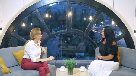 two women talking in an office free space sitting on sofas, multinational business women drinking coffee and chatting