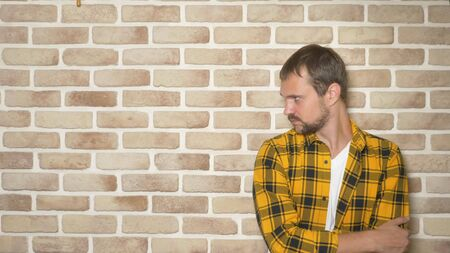 upset handsome man in a fashionably yellow checkered shirt against a brick wall, copy space. gestures and emotions concept