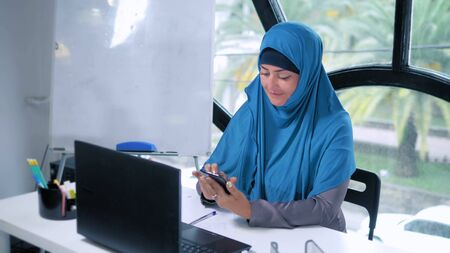 beautiful saudi business woman in hijab working in office using laptop, copy space