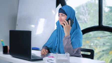 beautiful saudi business woman in hijab working in office using laptop and smartphone, copy space Stockfoto