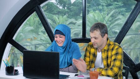 multinational team concept. muslim woman in hijab and caucasian man working together in the office using laptop. Stockfoto