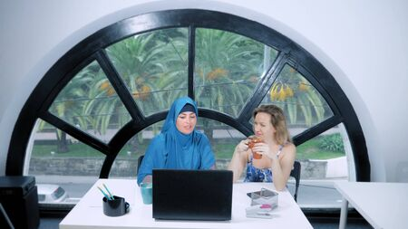 multinational team concept. Two women, a Muslim woman in a hijab and a Caucasian woman in an open top, work together at the office using a laptop.