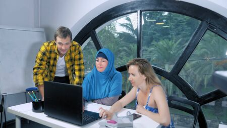 multinational team concept. muslim woman in hijab, caucasian woman and caucasian man working together in the office using laptop.